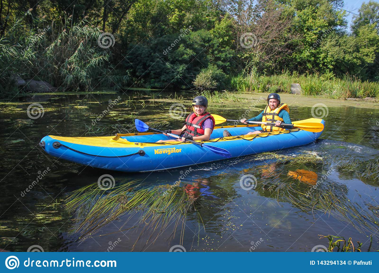 Happy young couple in life vests is smiling while sailing a kayak.