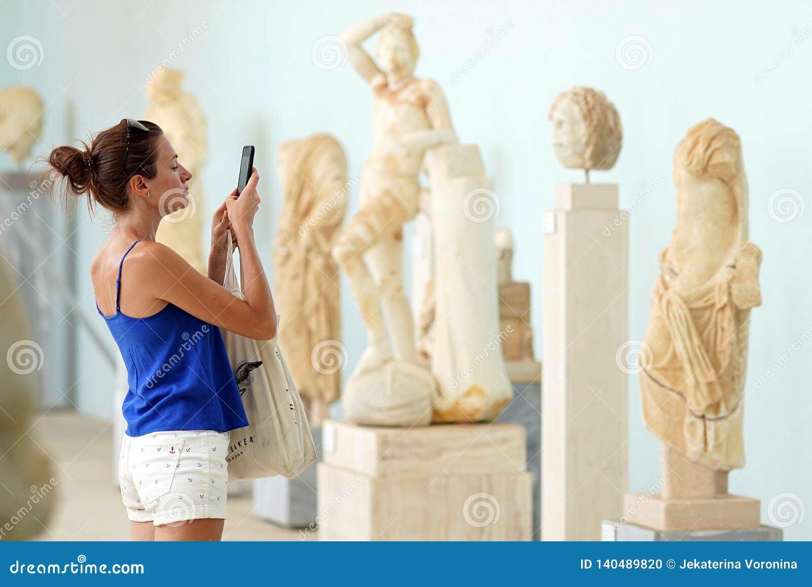 Mykonos Grekland, 11 September 2018, en turist tar fotografier i det arkeologiska museet