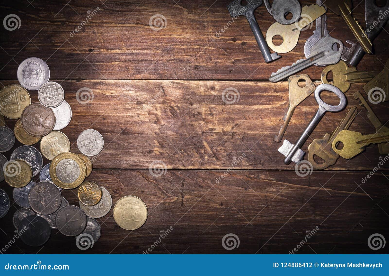 Mynt av olika länder och flera gamla tangenter på ett gammalt träbräde, ett tomt utrymme för text i mitt retro stil
