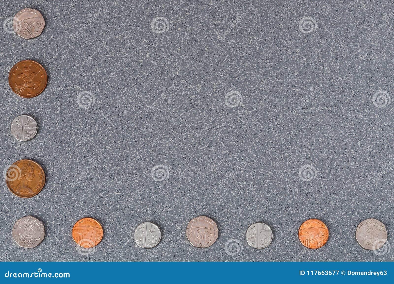 Mynt av Storbritannien av olik värdighet mot bakgrunden av grå granit