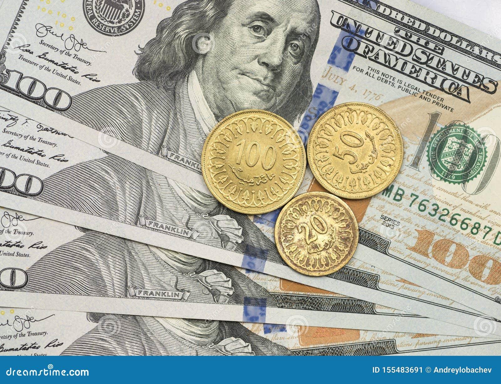 Mynt för tunisisk dinar överst av dollarräkningar