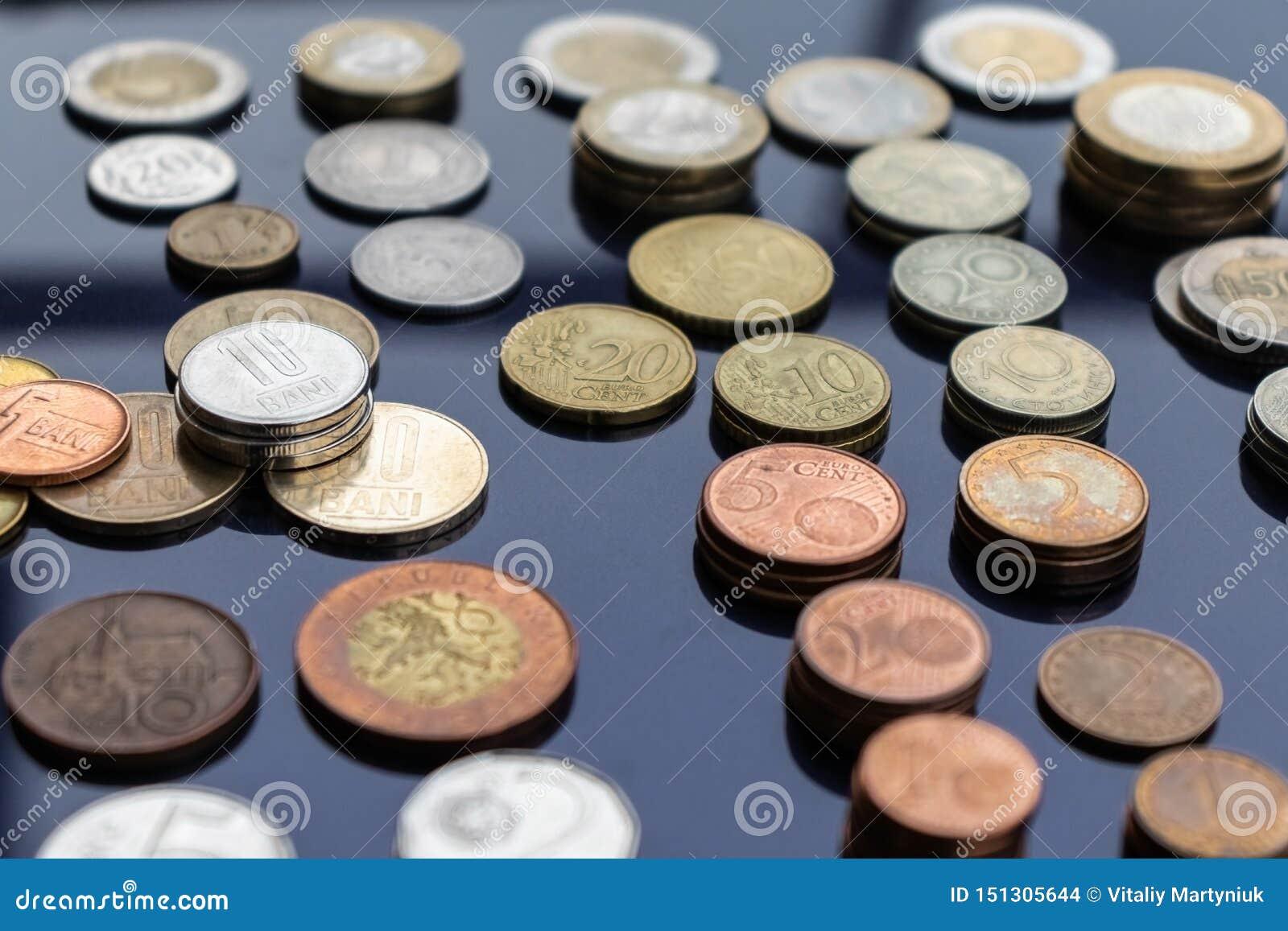 Mynt från olika länder läggas ut på buntar på en blå bakgrund