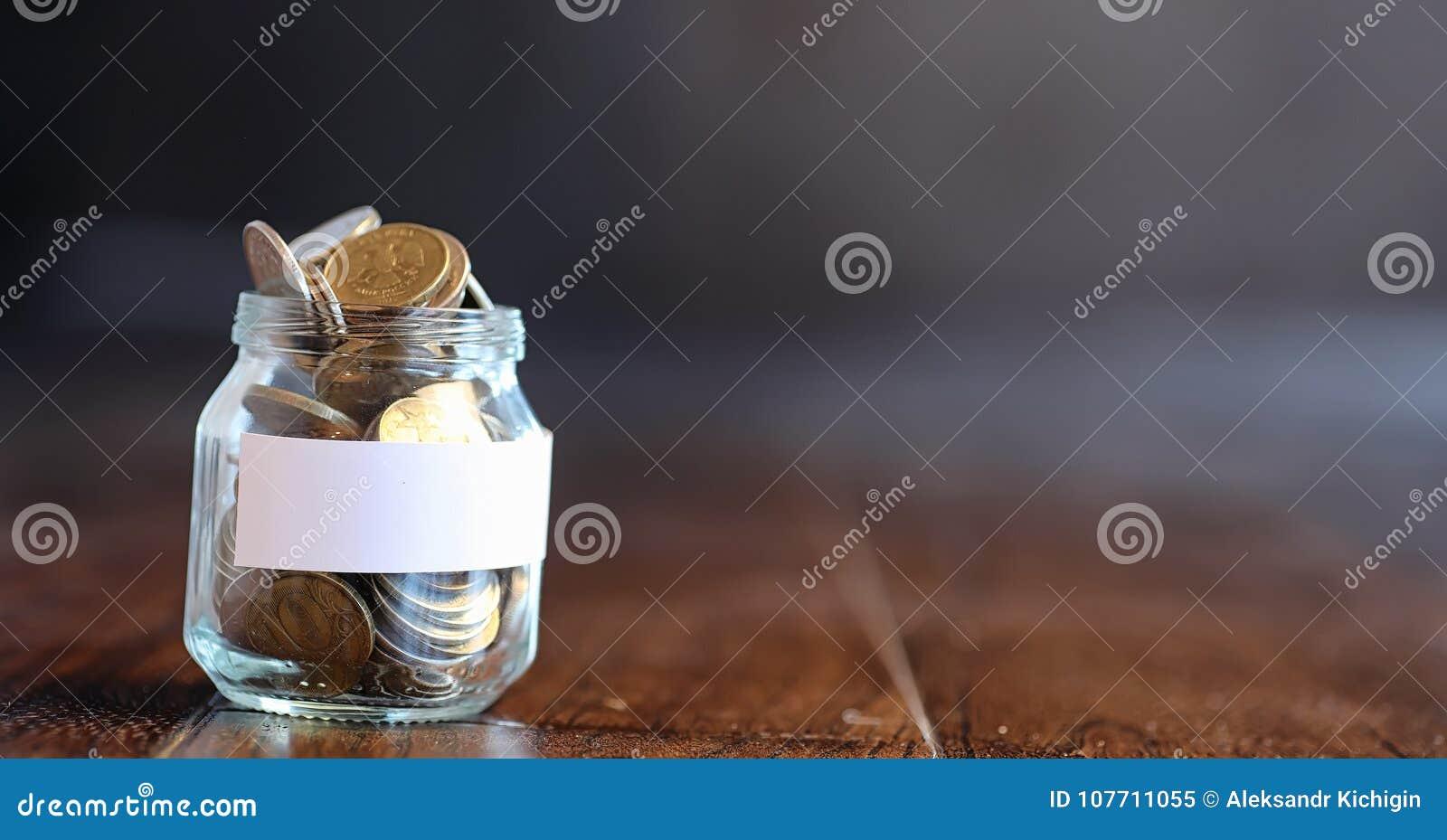 Mynt i en glass krus på ett trägolv Fick- besparingar från mynt