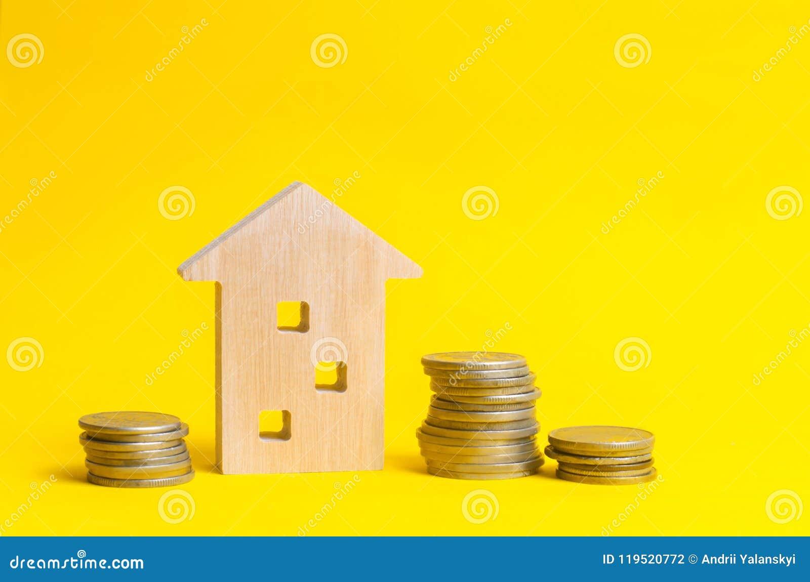 Mynt och trähus på en gul bakgrund verkligt begreppsgods Köpa, sälja och hyra ett hus Lån för en lägenhet,