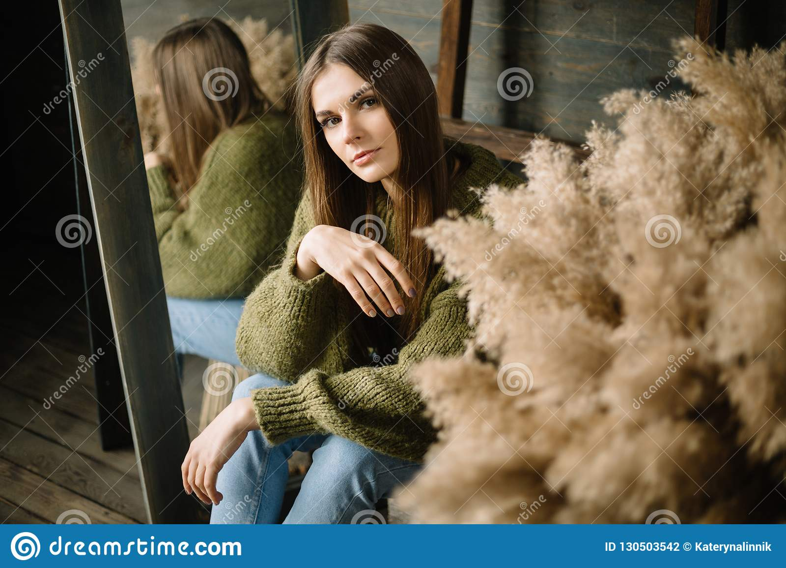 Mysterious smiling young girl in dark green knitted cozy sweater sitting on the floor. Studio conceptual photo