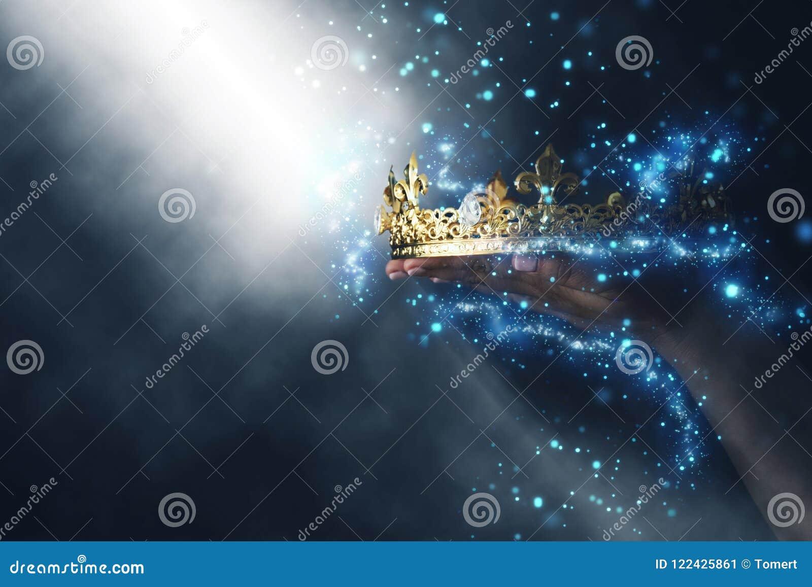 Mysteriousand magiczny wizerunek kobiety ` s ręka trzyma złocistą koronę