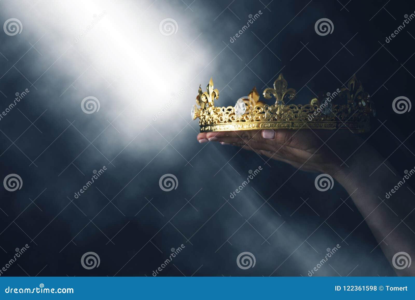 Mysteriousand magiczny wizerunek kobiety ` s ręka trzyma złocistą koronę nad gothic czarnym tłem średniowieczny okresu pojęcie
