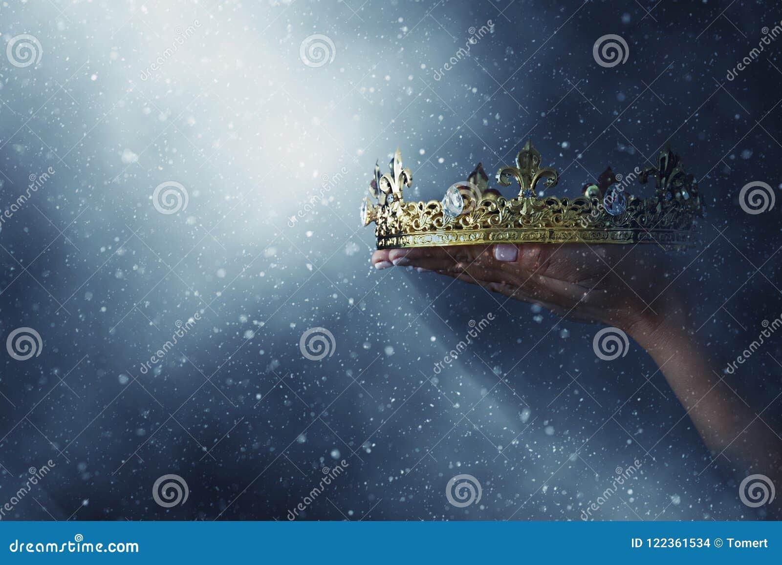 Mysteriousand magisch beeld die van vrouwen` s hand een gouden kroon over gotische zwarte achtergrond houden middeleeuws periodec