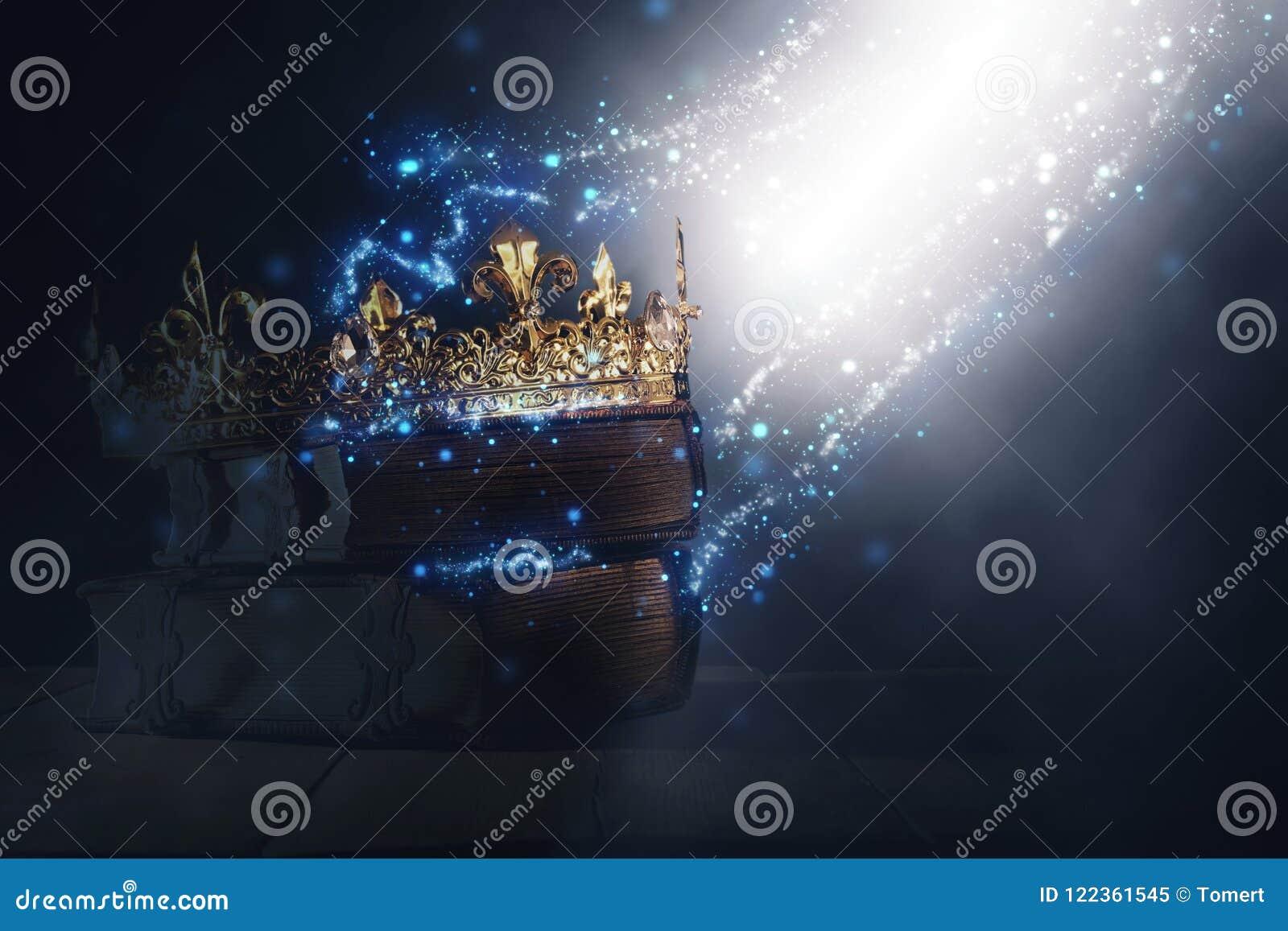 Mysteriousand magisch beeld van oud kroon en boek over gotische zwarte achtergrond middeleeuws periodeconcept