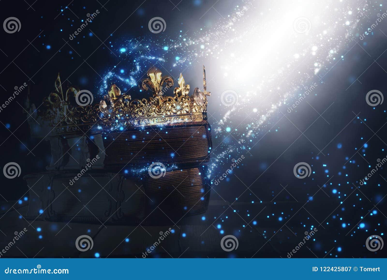 Mysteriousand magisk bild av den gamla kronan och boken över gotisk svart bakgrund medeltida periodbegrepp
