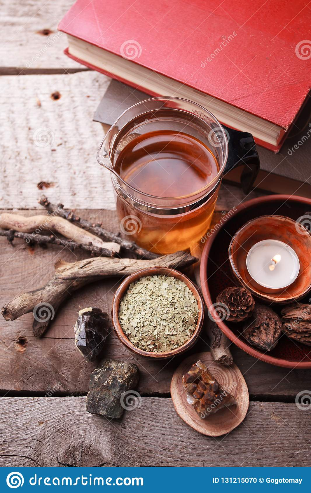Authentic interior details, glass of herbal rea, dry herbal plants, homeopathic treatment on rustic wooden background, alternative