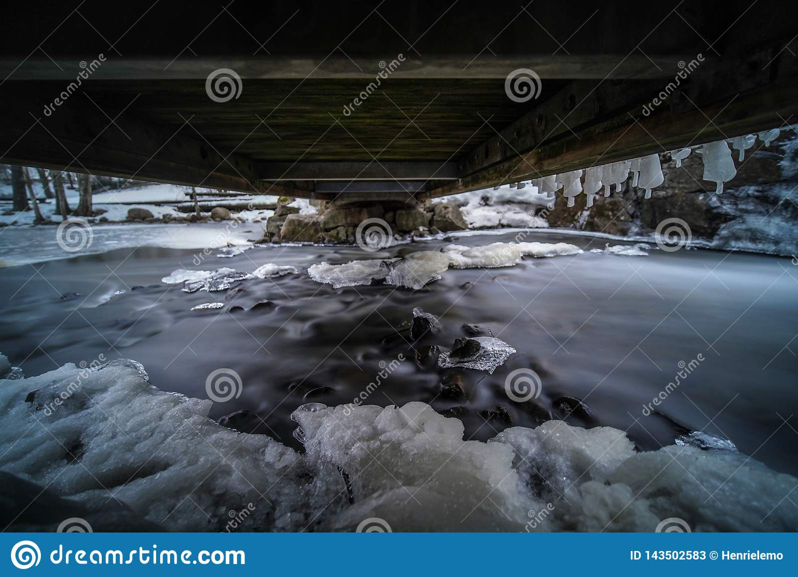 Mystiek beeld die van water onder kleine brug met ijs en koud weer stromen
