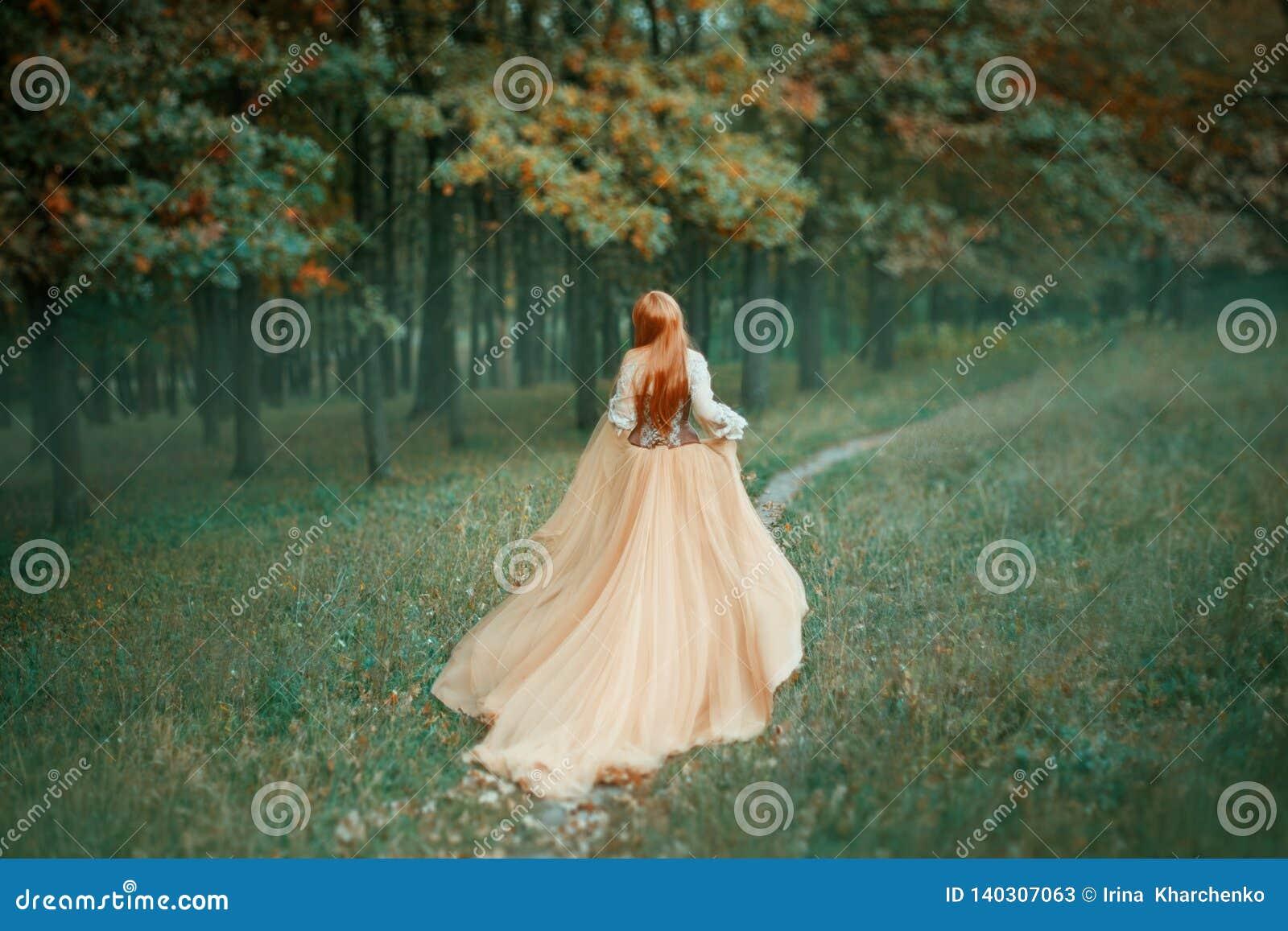 Mystisk dam i lång ljus dyr lyxig klänning med länge att skugga drevkörningar längs skogbanan, nya Cinderella