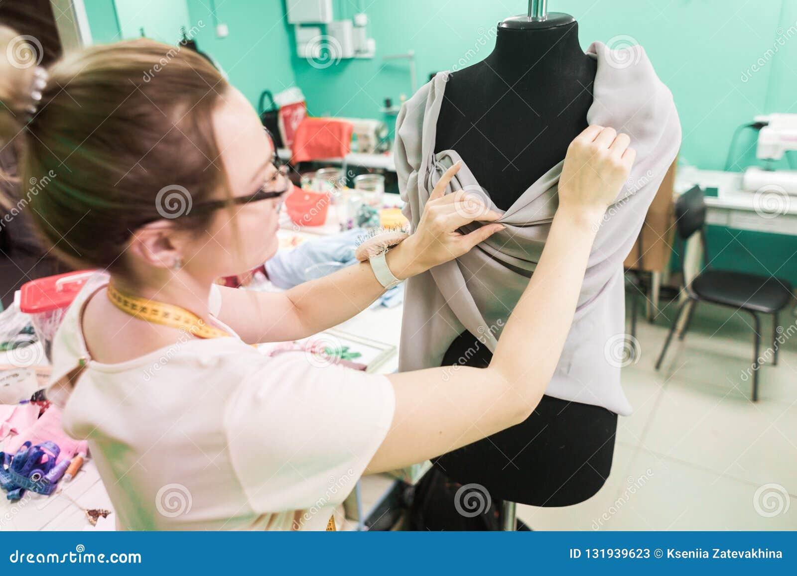 Nähende Werkstatt Näherin bei der Arbeit Junge Damenschneiderin, die an Kleid am Studio arbeitet