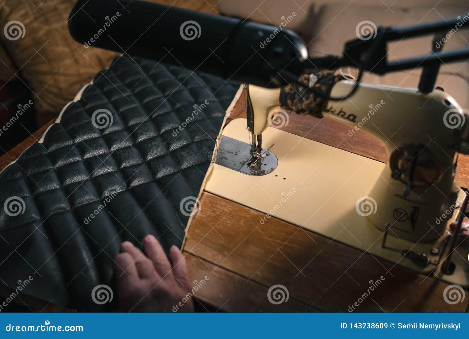 Nähender Prozess des Ledergürtels die Hände des alten Mannes hinter dem Nähen Lederne Werkstatt Textilweinlesenähen industriell