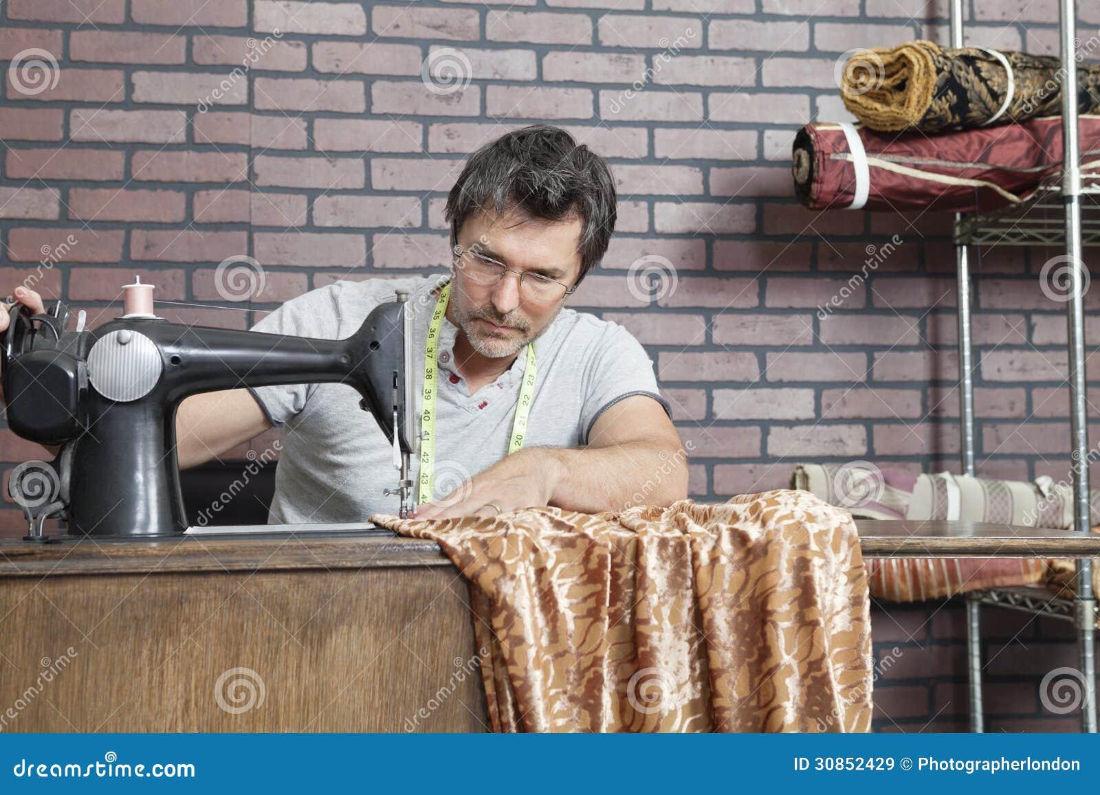 Nähender Stoff der reifen männlichen Damenschneiderin auf Nähmaschine