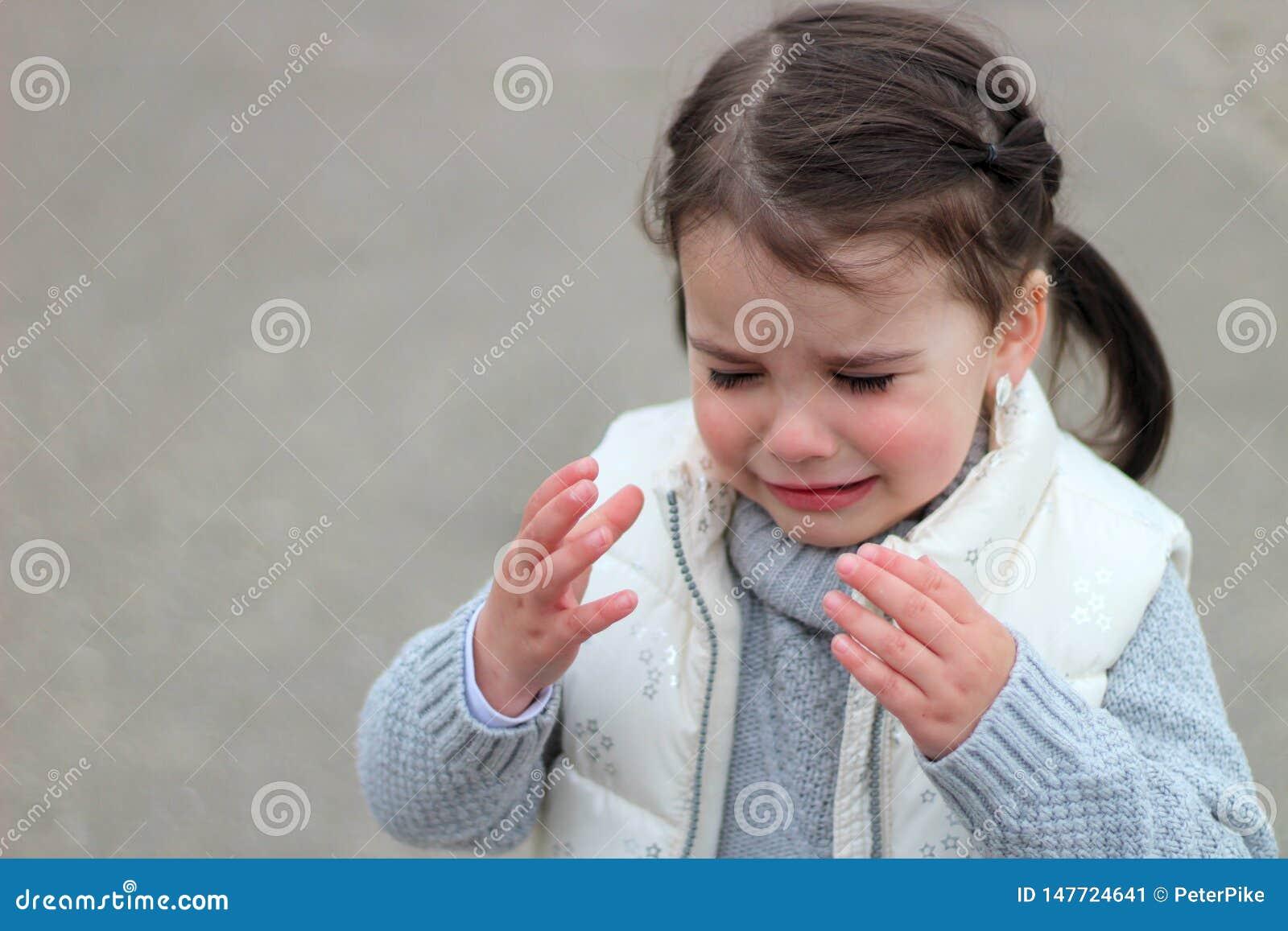 När du gråter flickan med råttsvansar i en tröja och en väst lyfter upp hennes händer