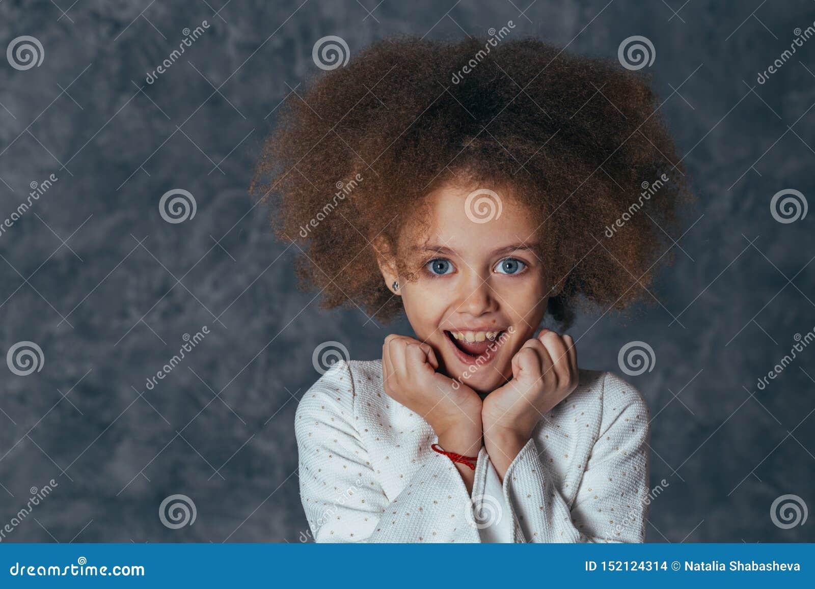 När du ler den nätta flickan med lockigt hår rymmer händer nära framsida och glädjas