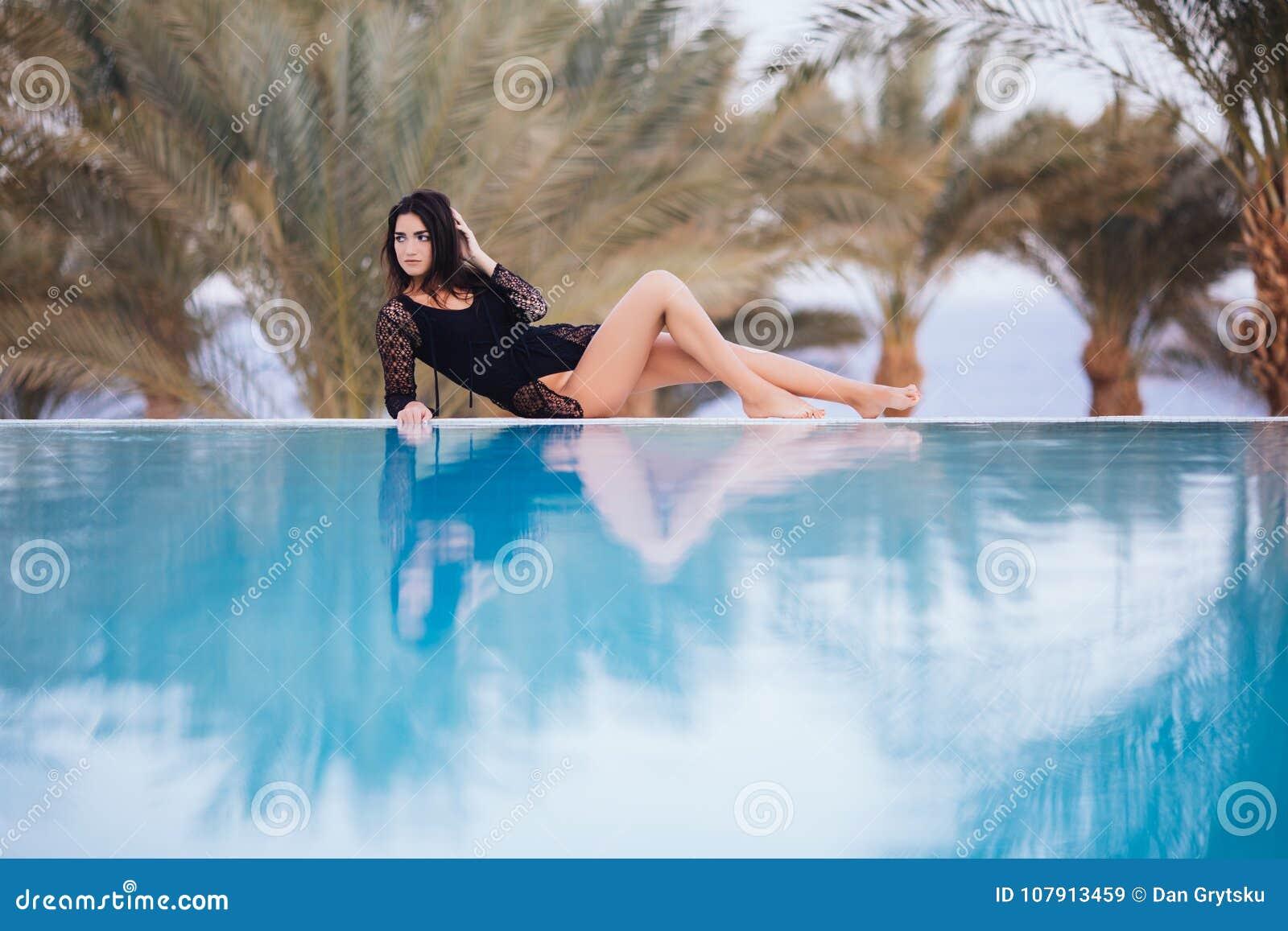 När du solbadar den unga härliga kvinnan som ligger på henne tillbaka på kanten av oändlighetspölen gömma i handflatan på, bakgru