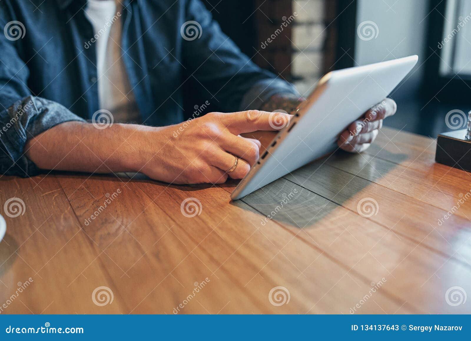 Nära övre handman som använder minnestavlan, förbindande wifi Funktionsdugligt precis från kafét