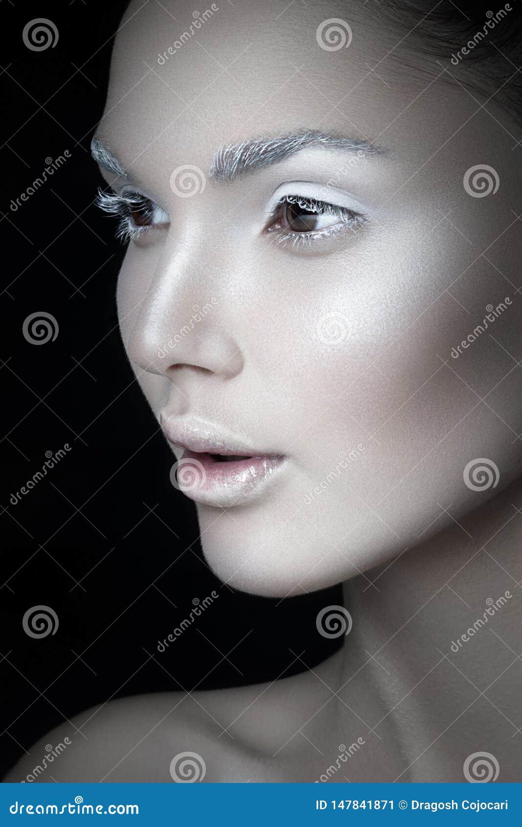 Nära övre profilstående av en ung kvinna, med konstnärlig makeup, på en svart backgorund id?rikt begrepp