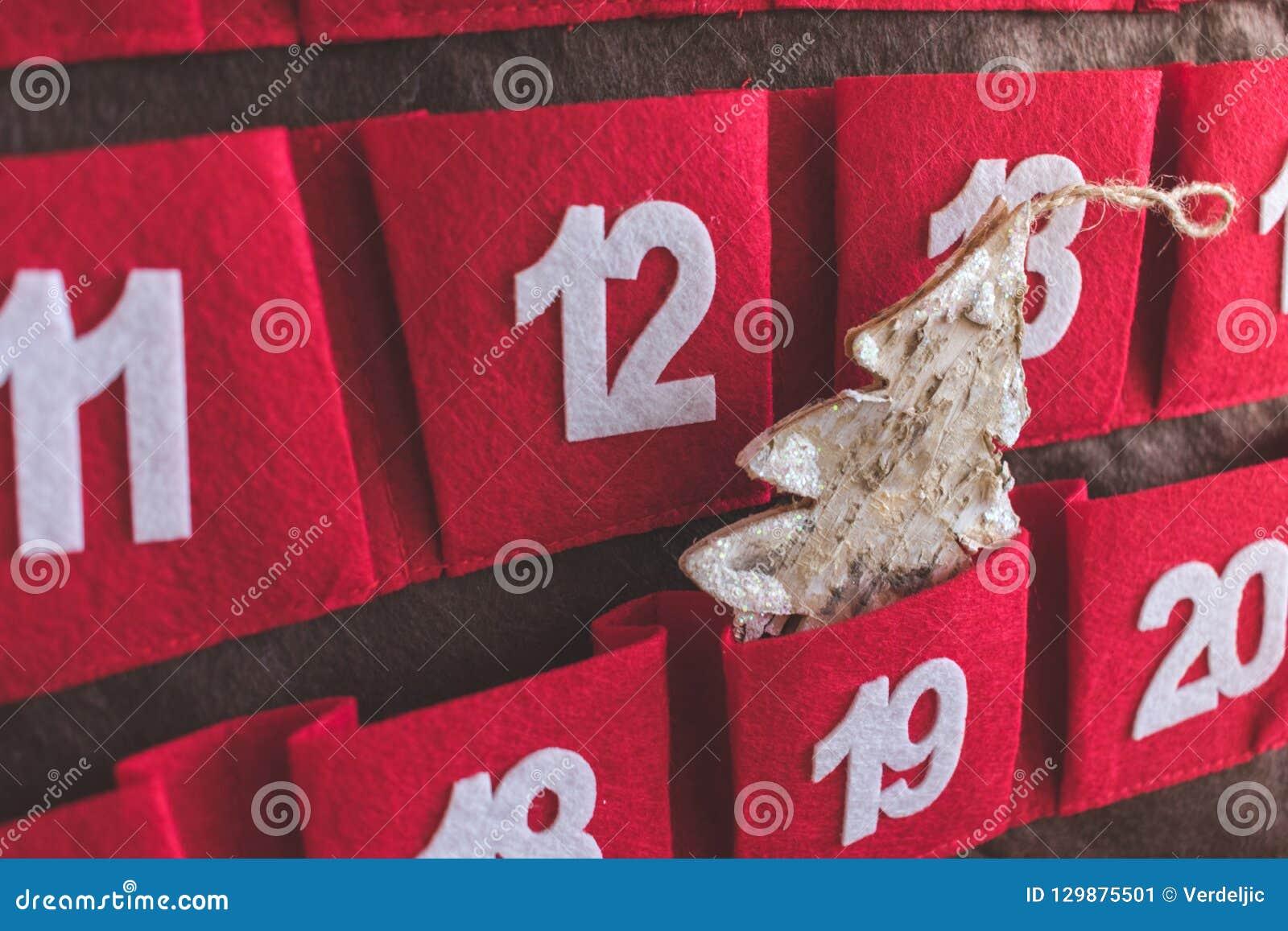 Nära övre sikt av en röd och brun textilAdventkalender med data och en julgrangarnering i ett fack