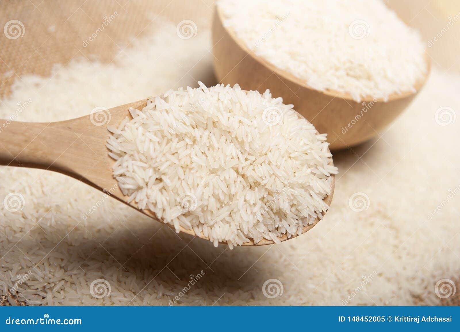 Nära övre sikt av ris i en träsked och bunke på träbakgrund