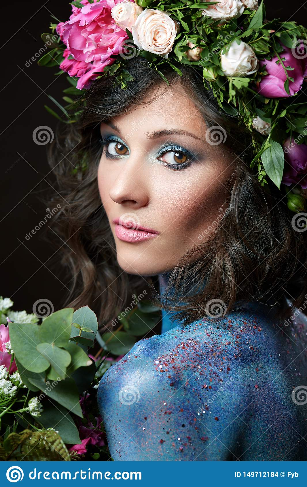 Nära övre skönhetstående av en ung kvinna med peones