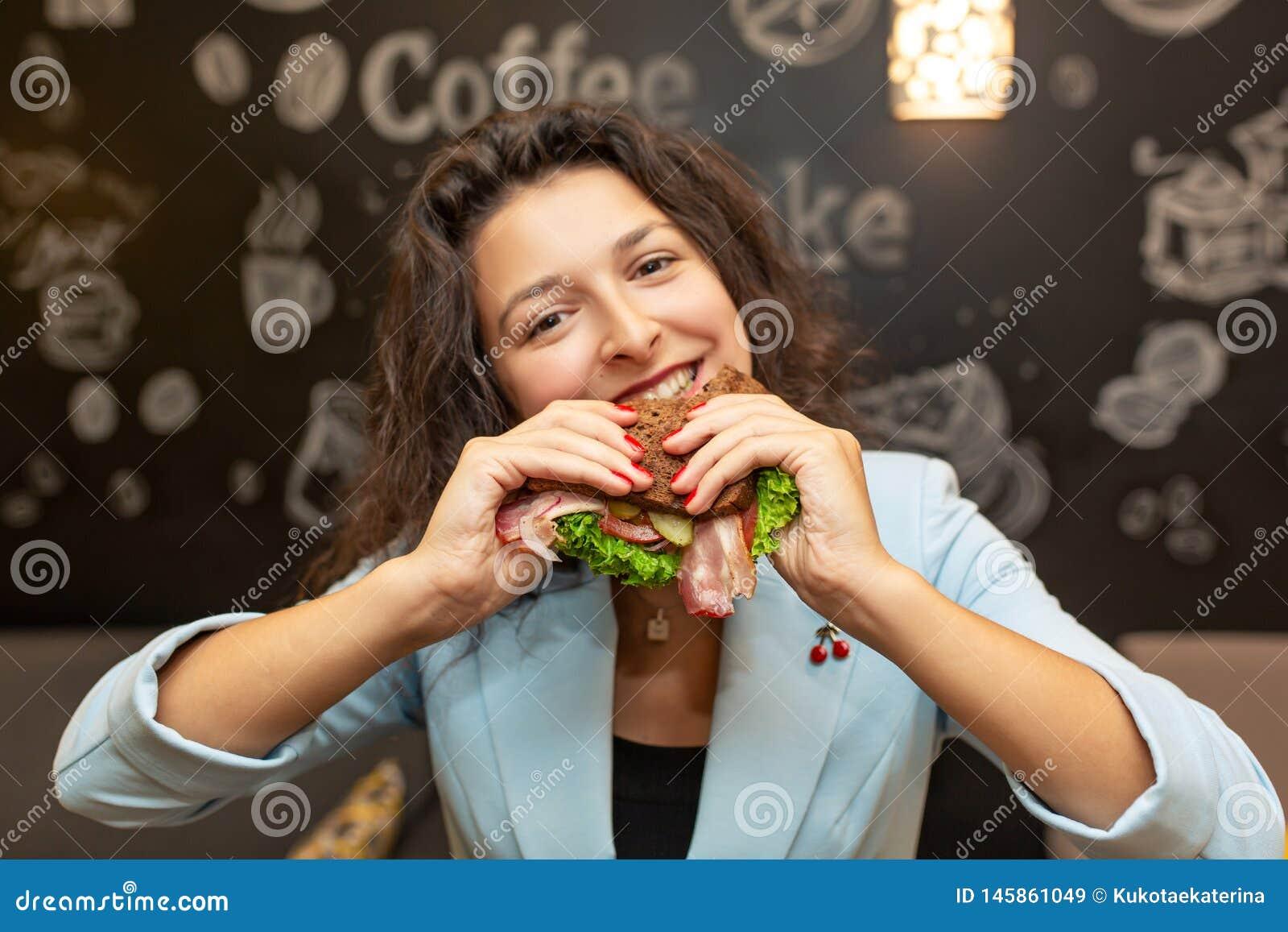 Nära övre stående av den hungriga unga caucasian kvinnan, tuggasmörgås