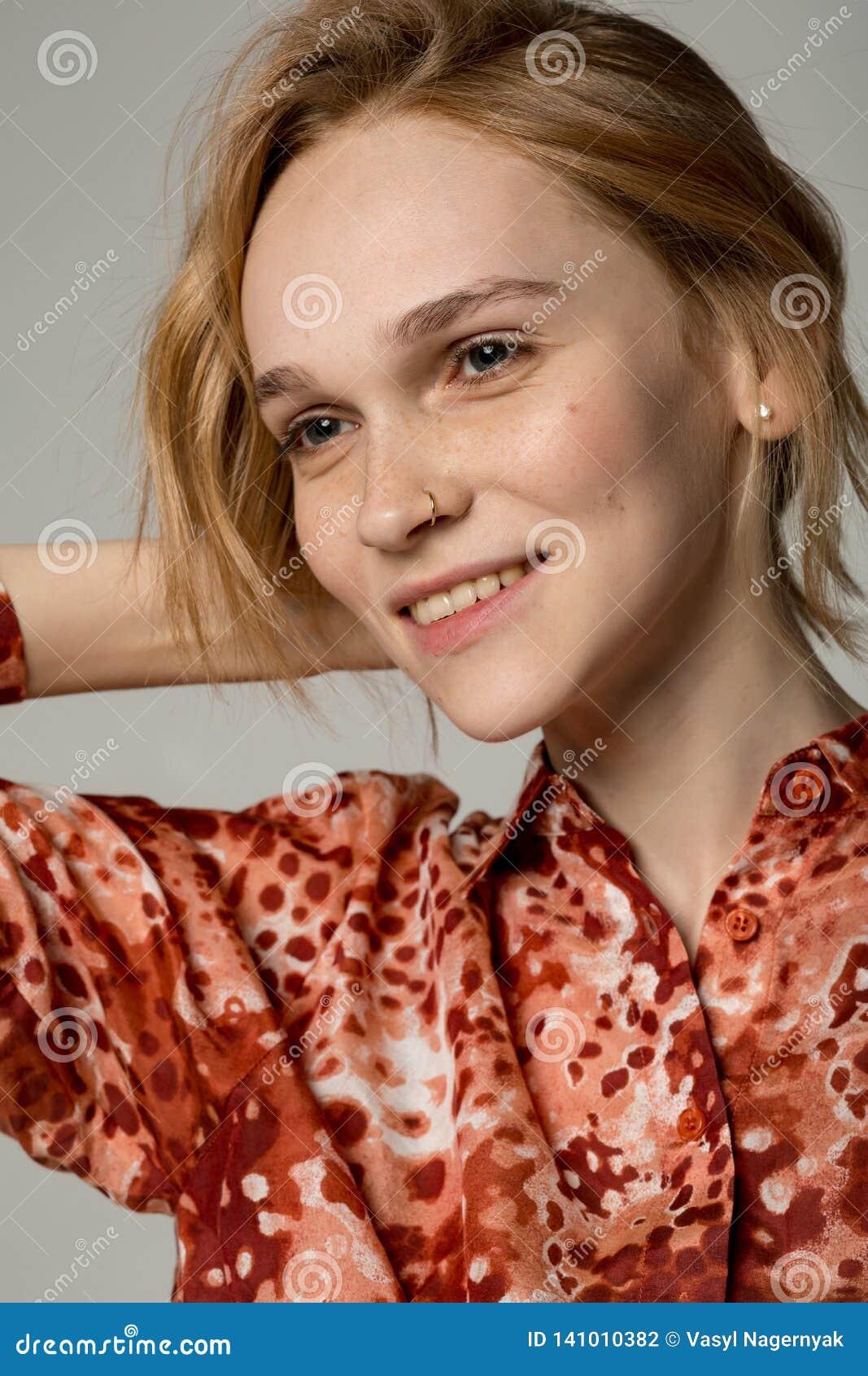Nära övre stående av den unga kvinnan med lockigt blont hår som tränger igenom i näsan