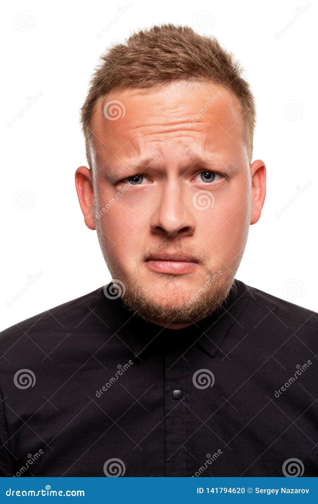 Nära övre stående av en säker, blond stilig ung man som bär den svarta skjortan som isoleras på vit bakgrund