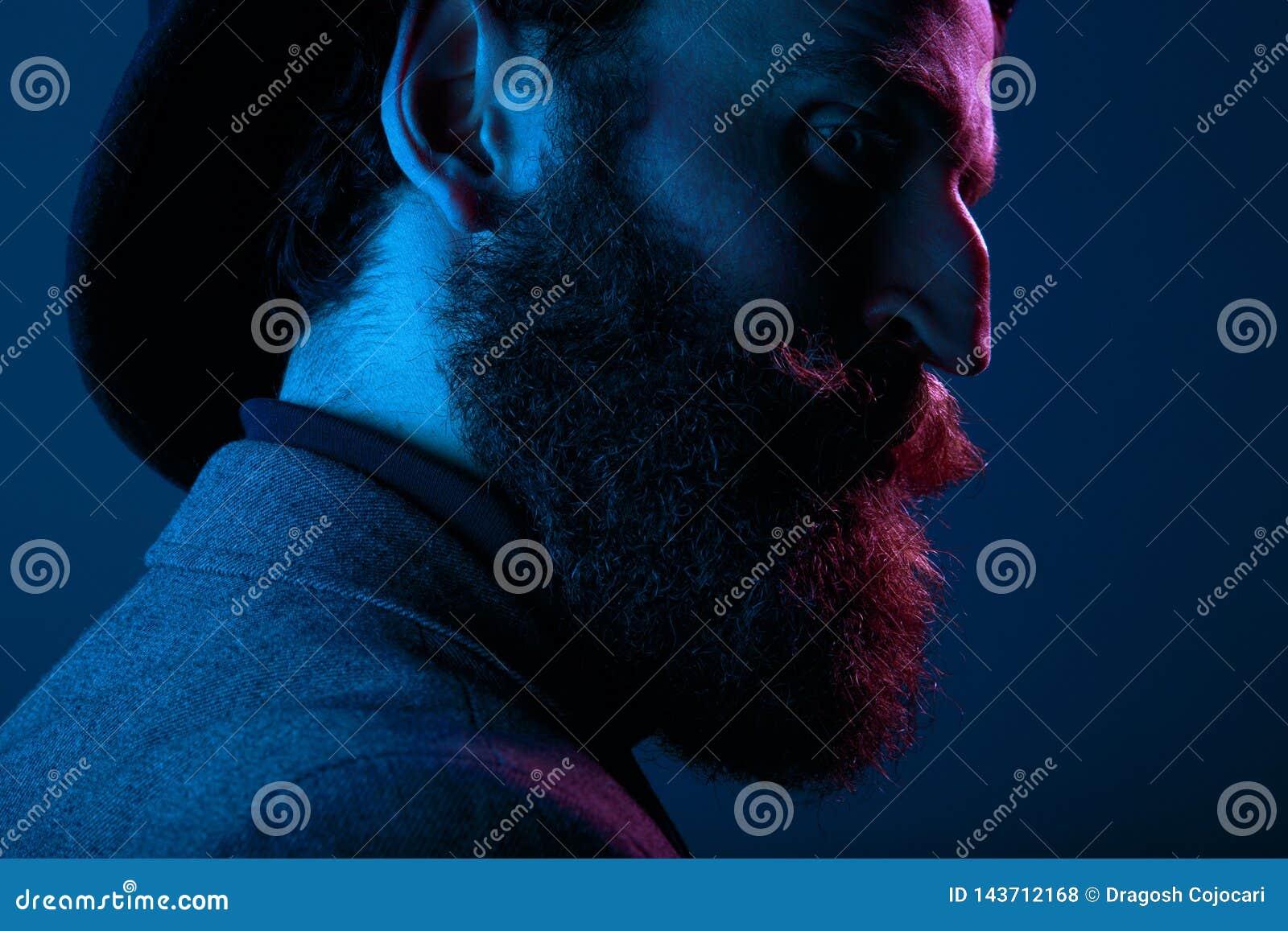 Nära övre stående av en skäggig man i elegant hatt och dräkten som poserar i profil i studion som isoleras på blå bakgrund