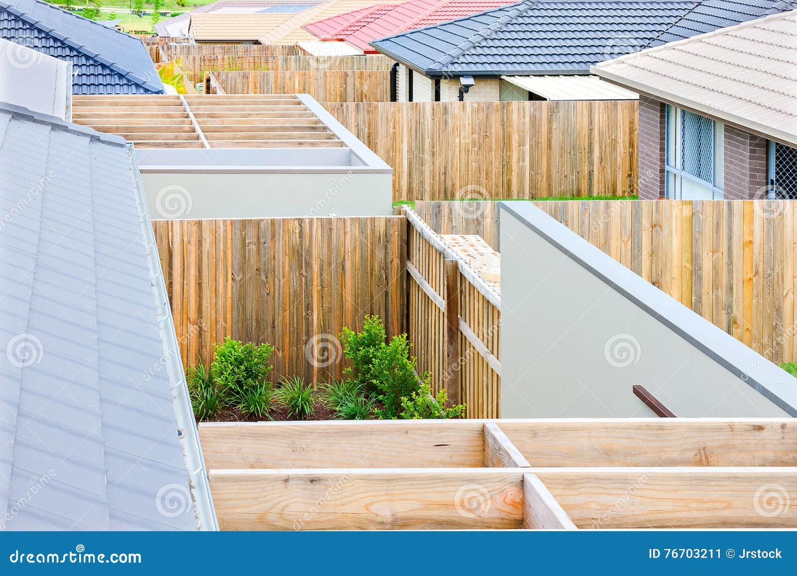 Nära sikt av trästrålar med staket av hus av en by
