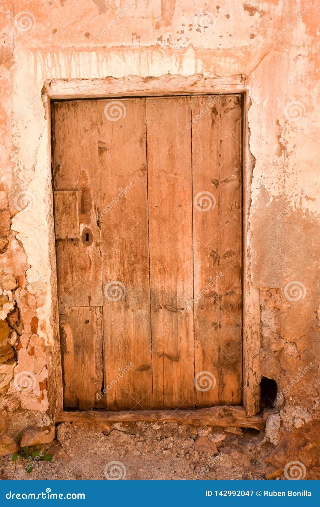 Nära upp av en gammal trästängd dörr i en vägg av betong, gyttja och stenen i ett stängt övergett hus var inget bor