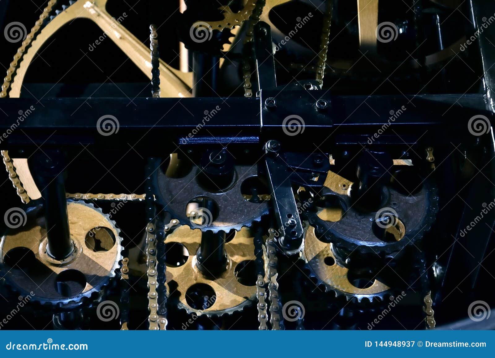 Närbild av den öppna mekanismen av en tappningklocka med guld- kugghjulhjul och kedjor
