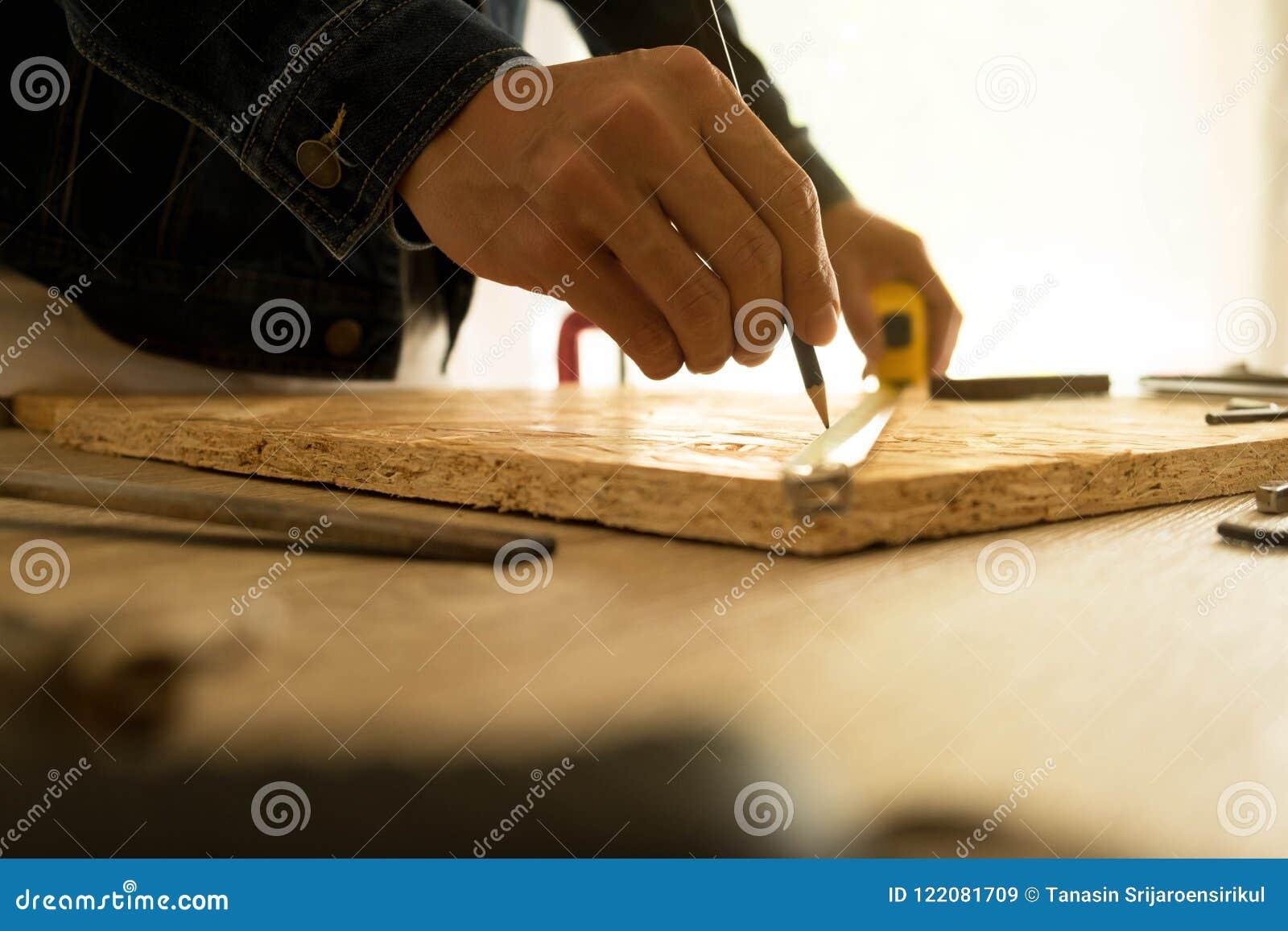 Närbild av den manliga snickaren som rymmer ett måttband i seminarium