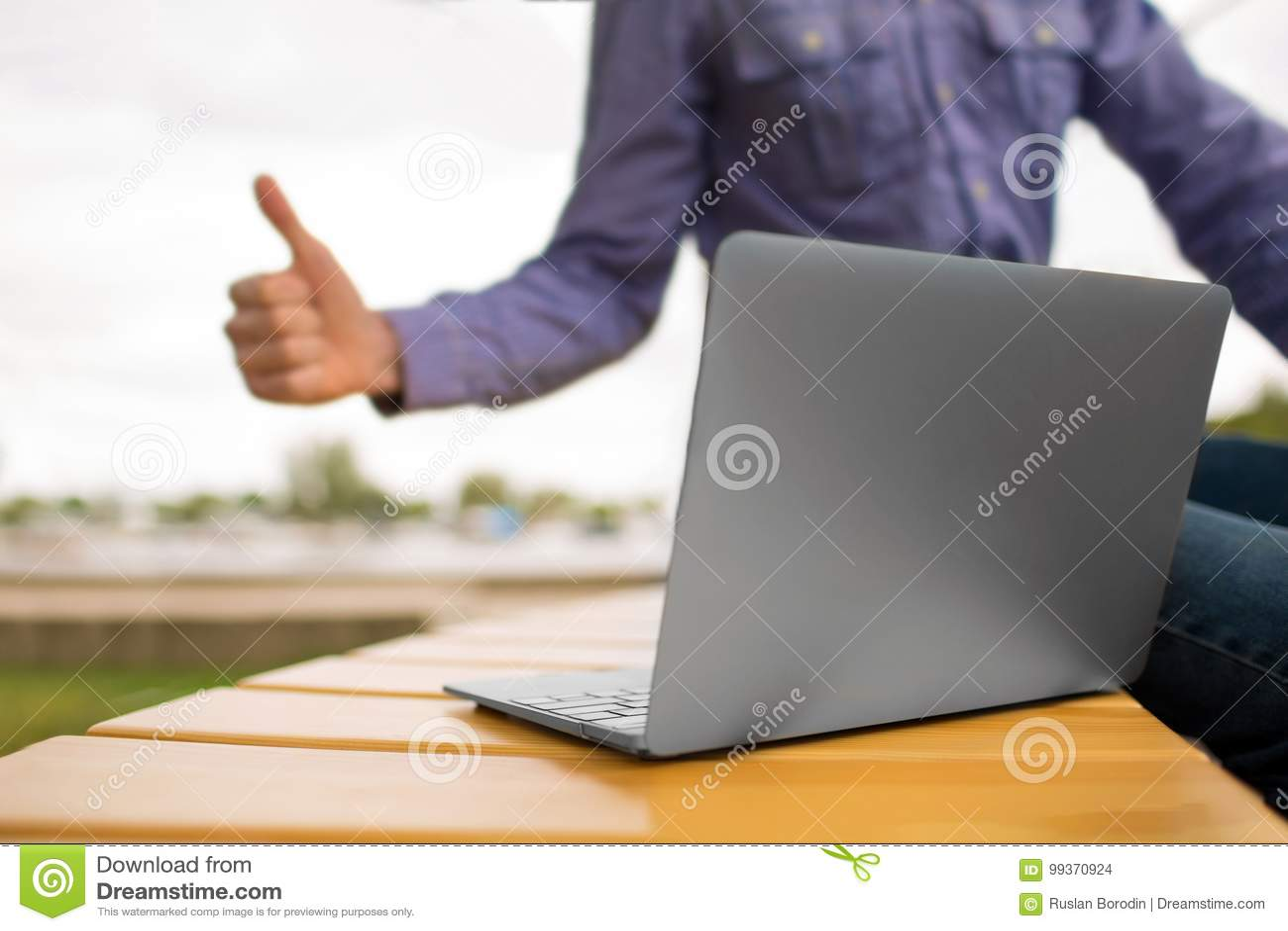 Närbild av en bärbar dator Bärbar dator på en bänk på en suddig bakgrund Ung man som upp till ger en tumme en bärbar dator kopier