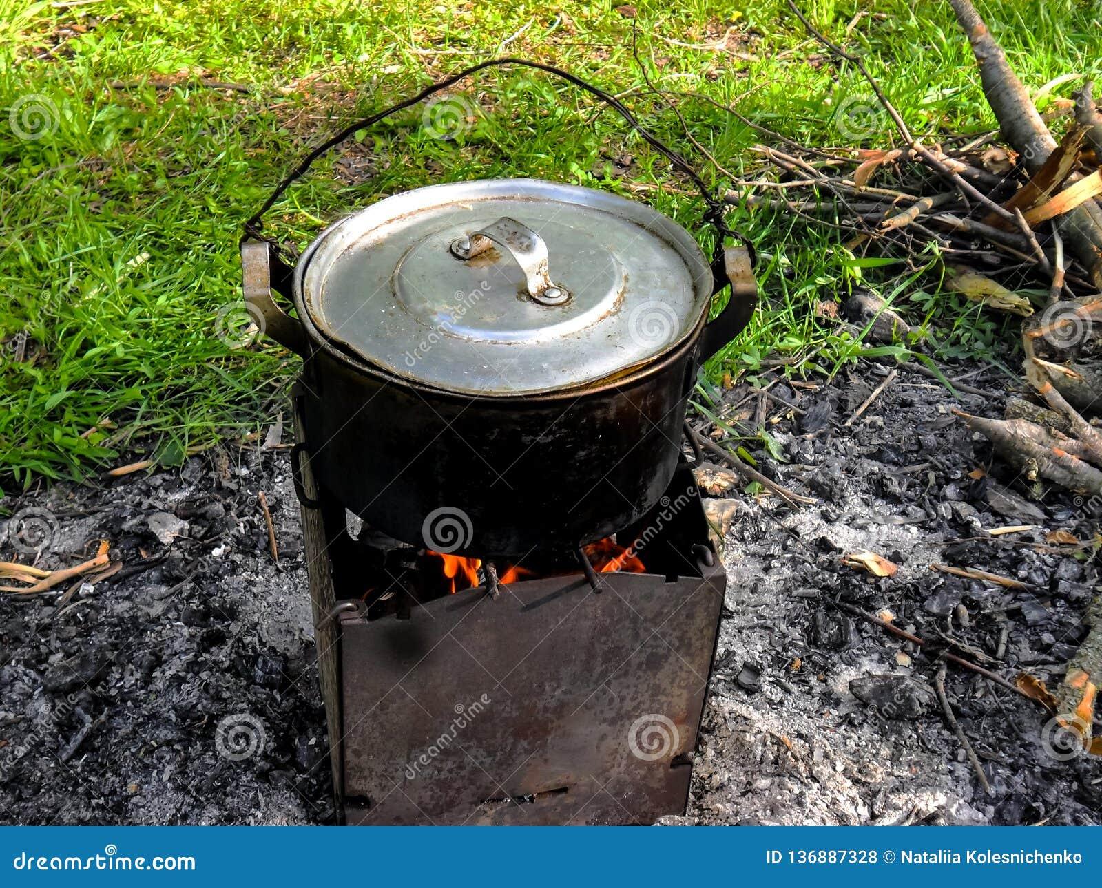 Närbild av en campa panna för att laga mat fisksoppa som fångades på betet med en härlig landskapbakgrund