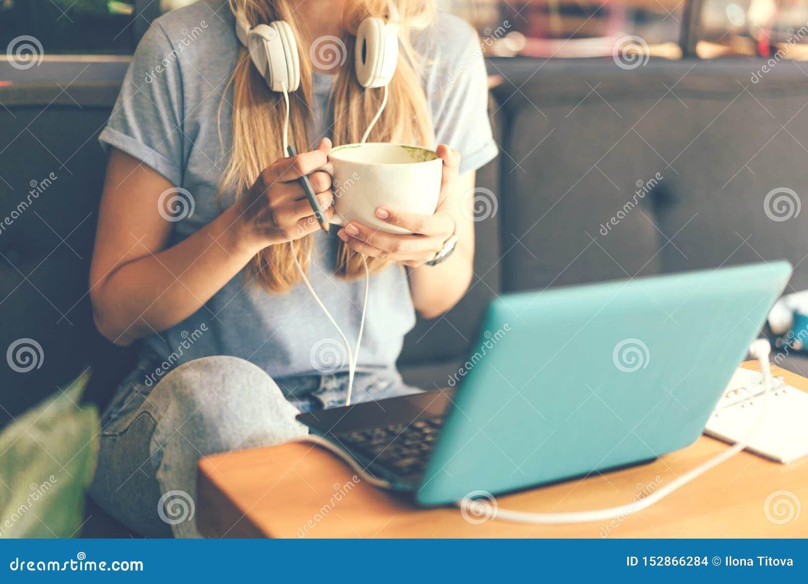 Närbild av en flicka med hörlurar och en bärbar dator