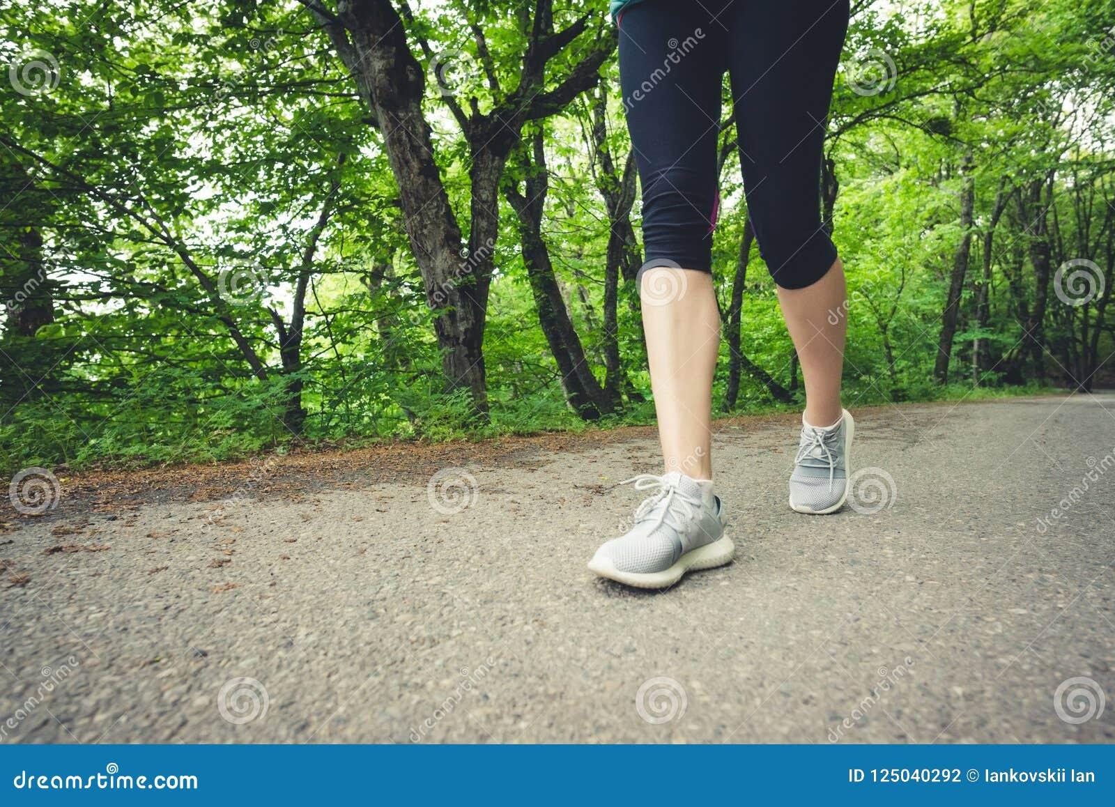 Närbild av en fot av en sportig flicka i damasker och gymnastikskor, innan att jogga i skogen begreppet av utomhus- sportar