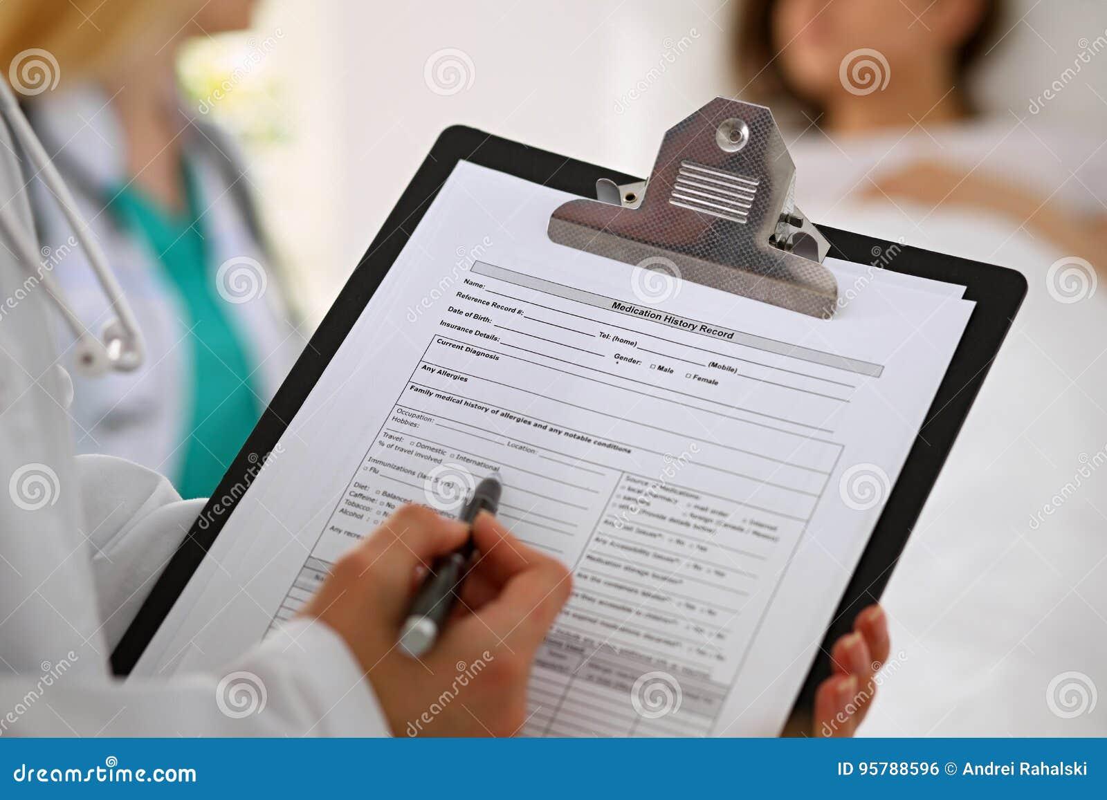 Närbild av en kvinnlig doktor medan rekord för medicinsk historia för påfyllning