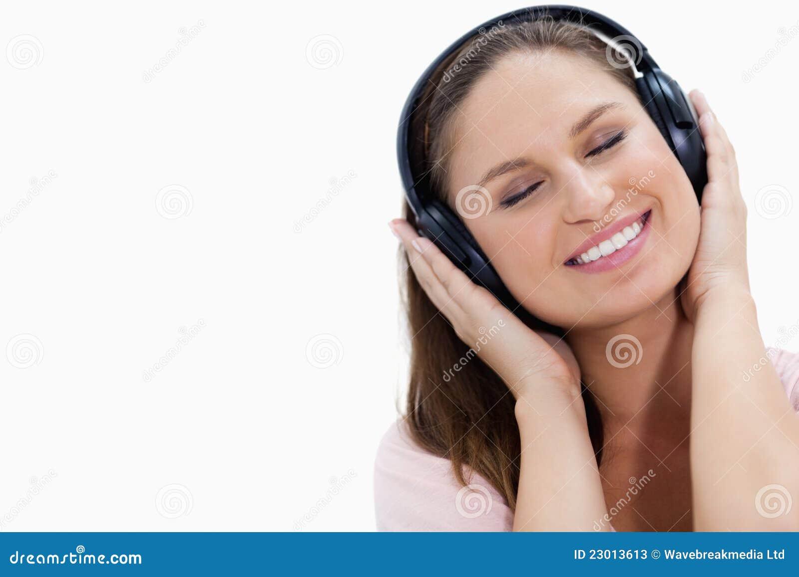 Närbild av en le flicka som lyssnar till musik