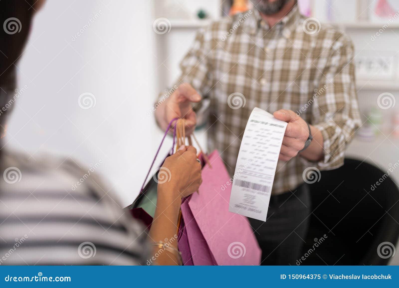 Närbild av en säljare som ger en klient med shoppingpackar