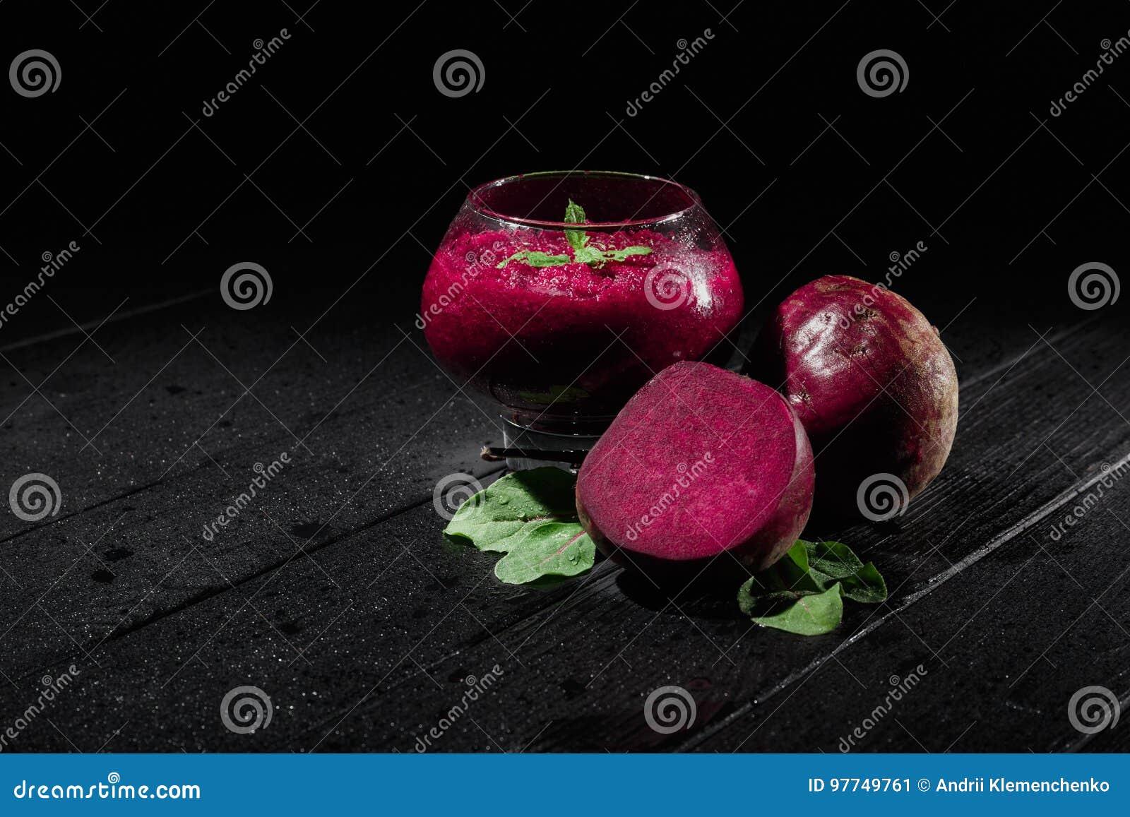 Närbild av ett genomskinligt exponeringsglas med detfärgade mellanmålet på en svart bakgrund Sund mat med beta, mintkaramellen oc