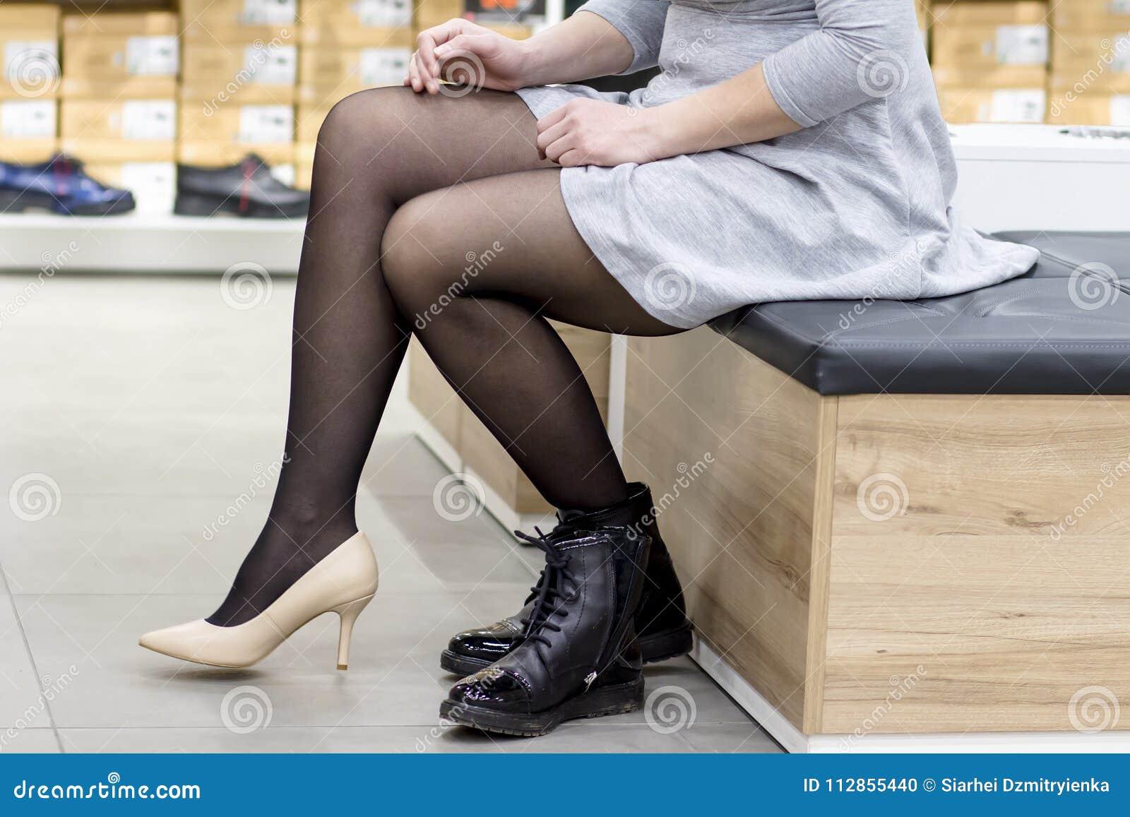 Närbild av flickan som försöker på nya modeskor i skolager den unga kvinnan klär ursnygga skor i boutique av trendiga skor