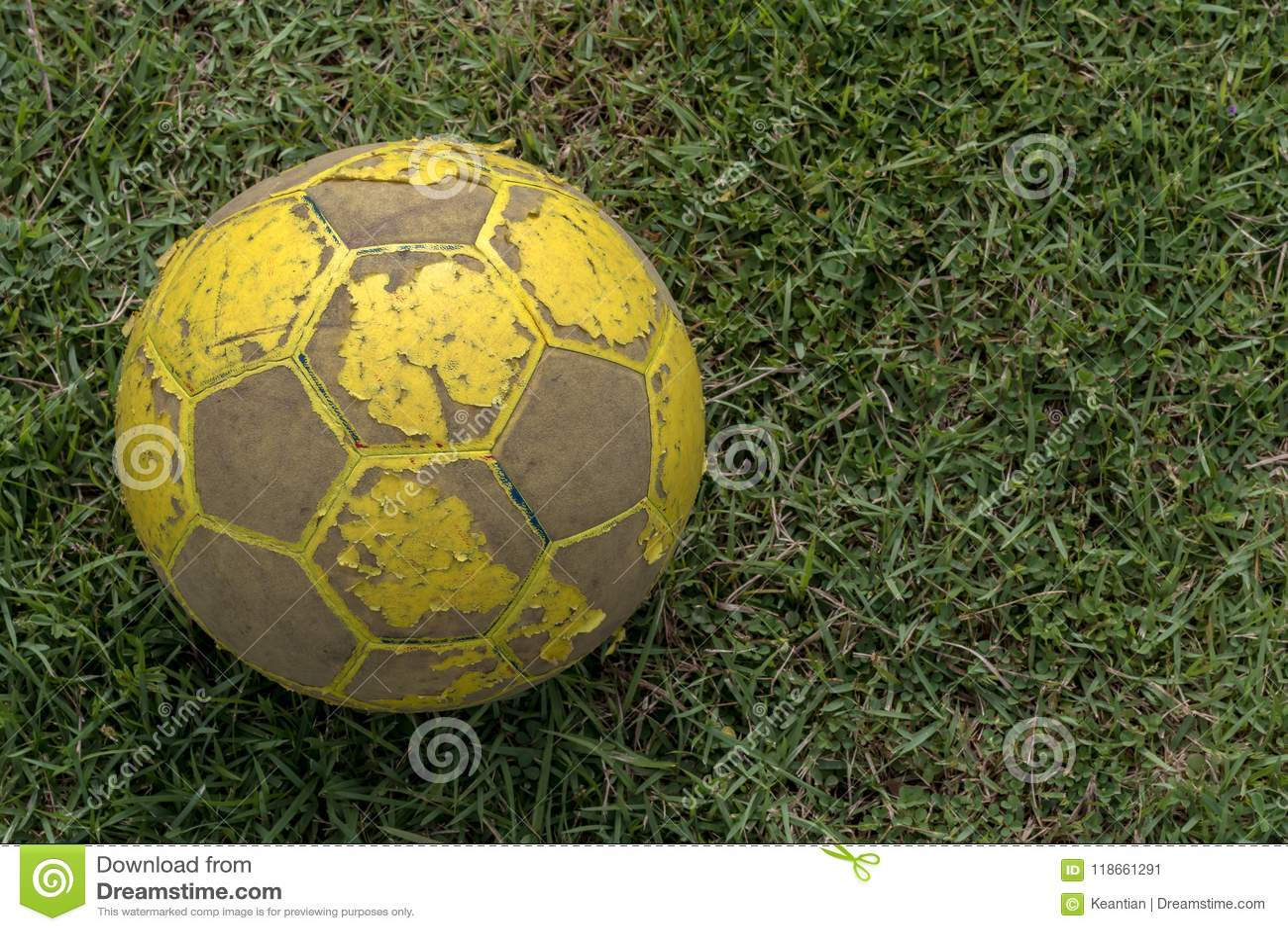 Närbild av gammal fotboll som ligger på gräs