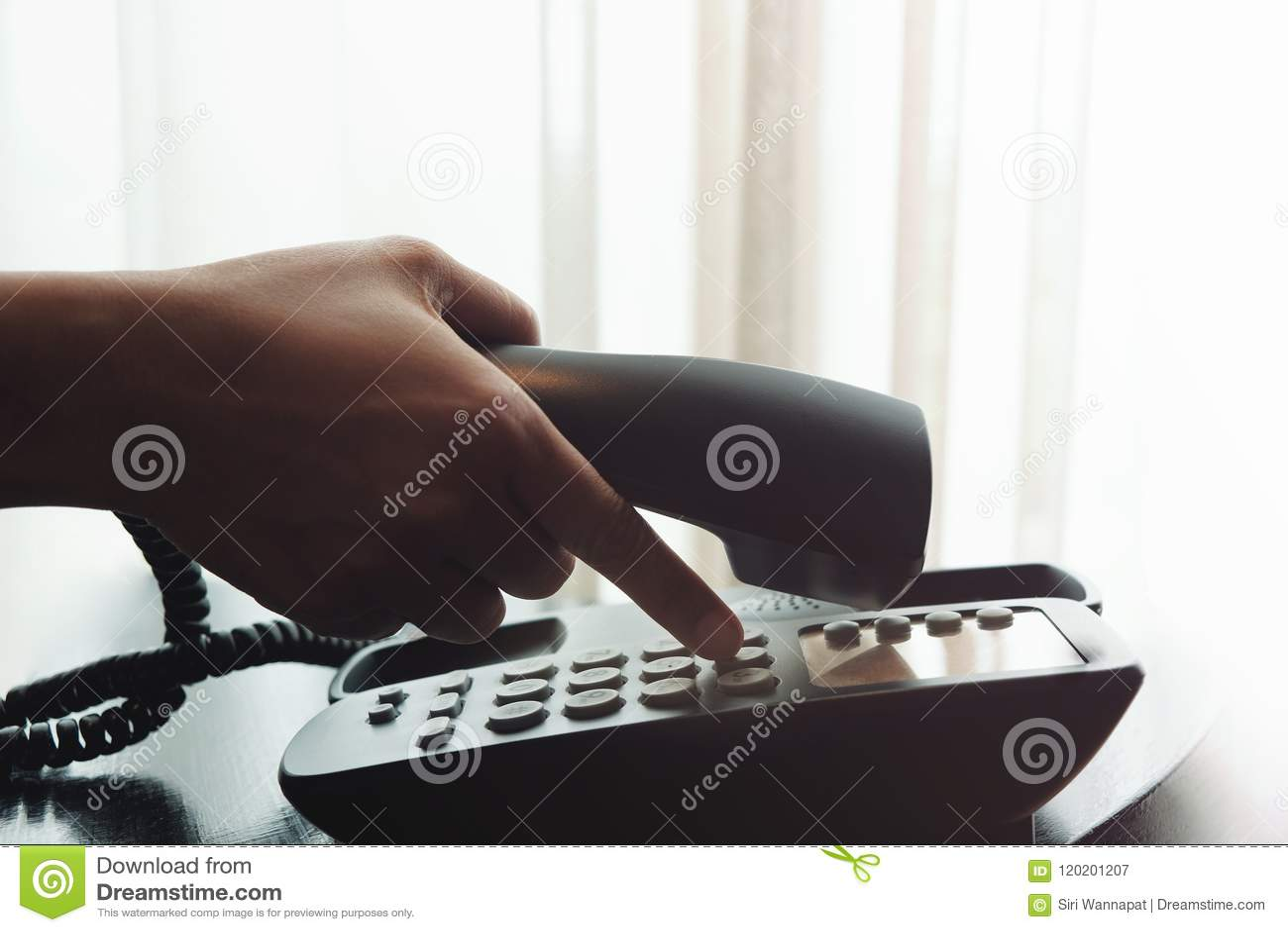 Närbild av handen för kvinna` s genom att använda en telefon i hus- eller hotellnea