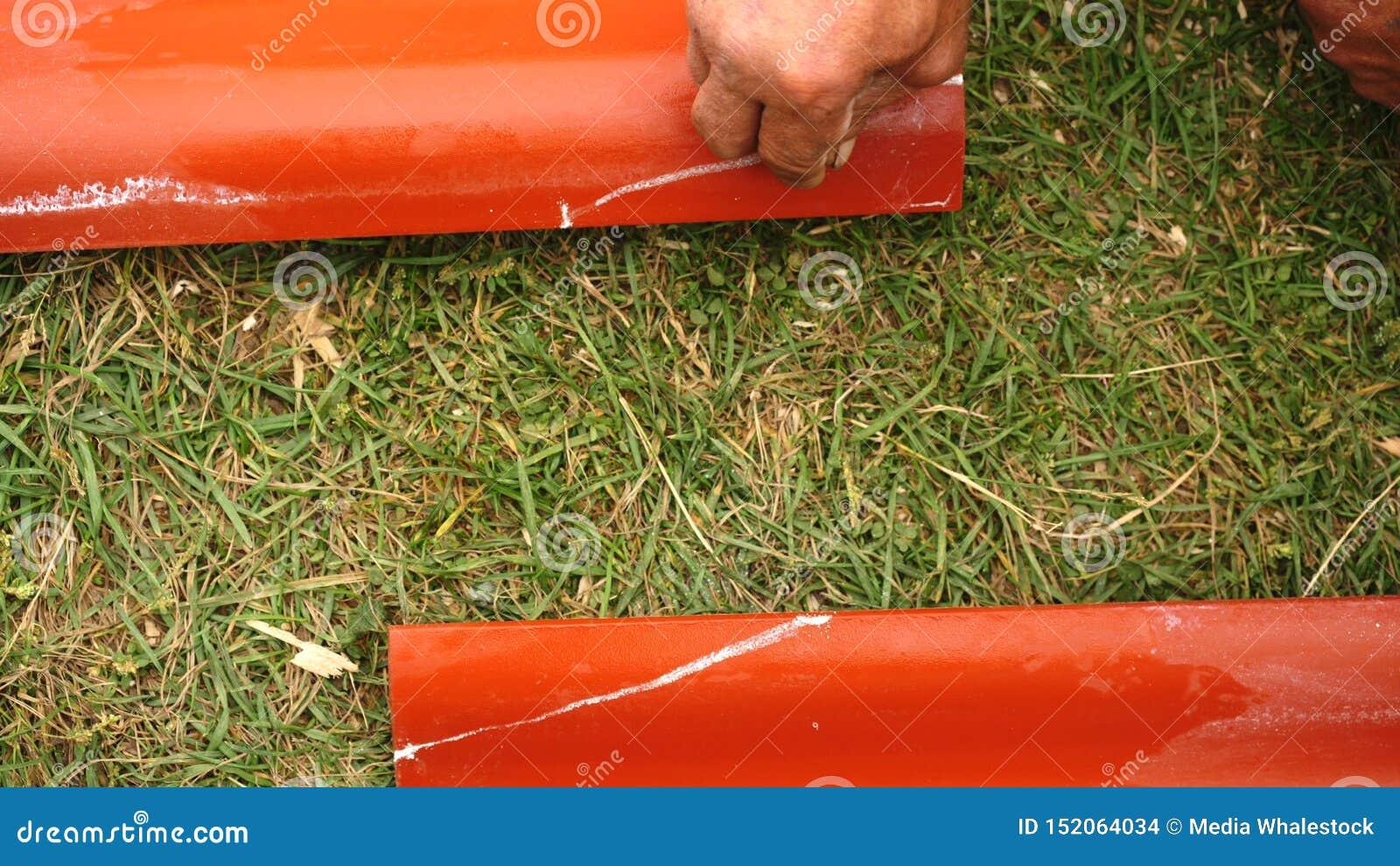 Närbild av manlig arbetares hand som gör mätningar på det röda stålet som taklägger det fria gem Material och utrustningar för