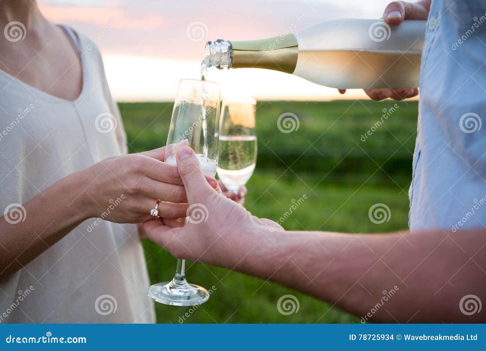 Närbild av par som har champagne i fält