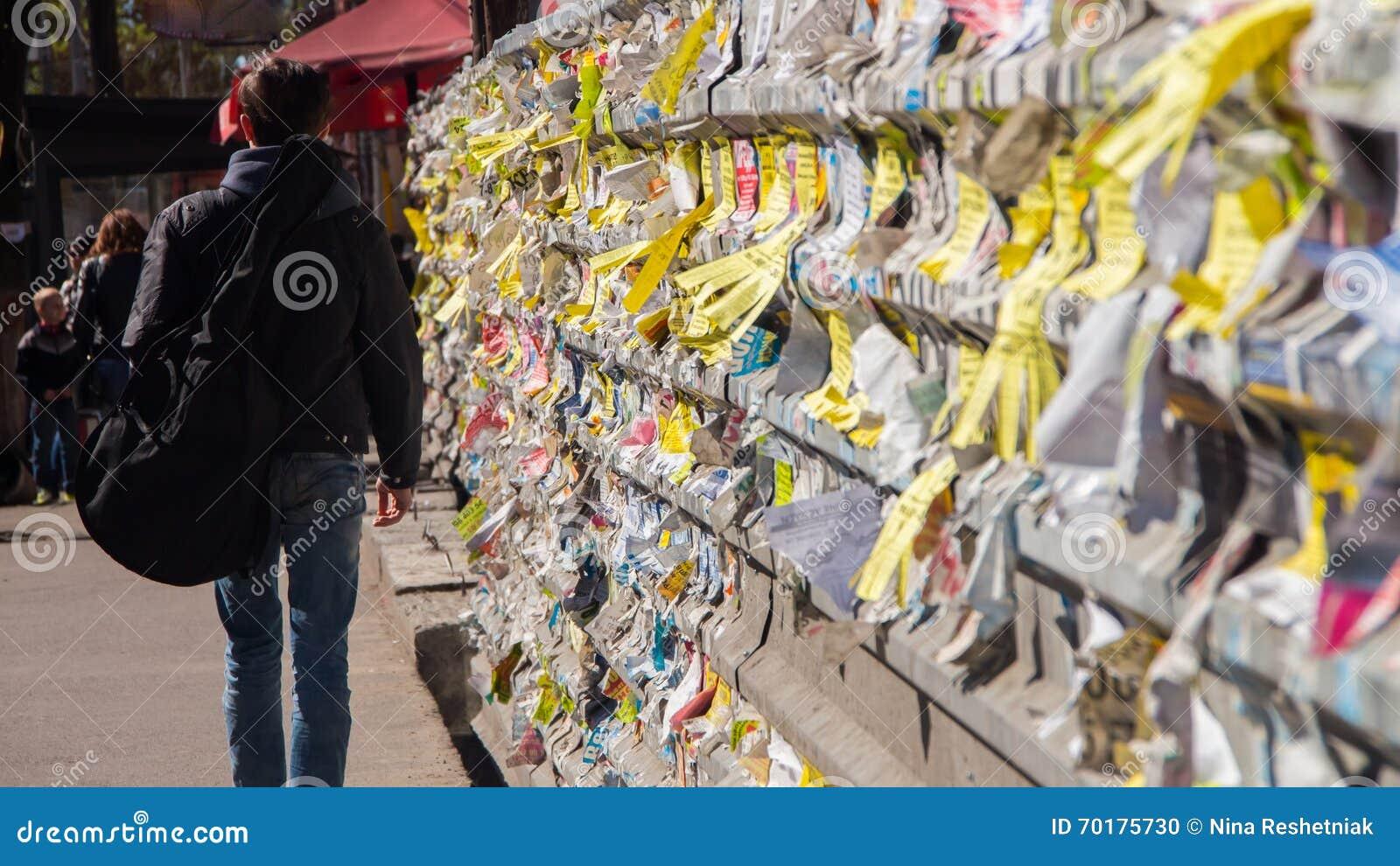 Närbild av sönderrivna annonser på väggen